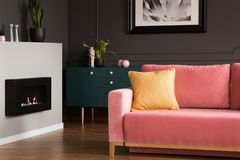 Yellow pillow on a powder pink, velvet sofa and a black, eco burning fireplace in a modern vintage living room interior stock image