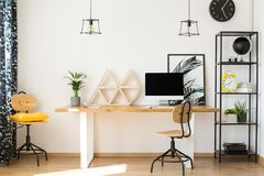 Neutral work zone with decor. Yellow pillow on wooden chair next to table with geometric decor and desktop in neutral work zone Royalty Free Stock Photography