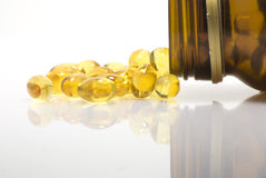 Yellow pills. Yellow oval pills and bottle with reflection Stock Photography