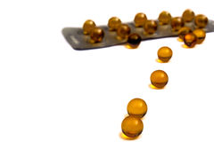 Yellow pills. Path from yellow pills conducts to packing on a white background Royalty Free Stock Images