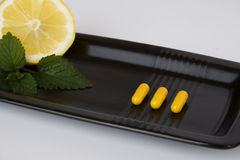 Yellow pills on black plate Royalty Free Stock Image