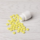 Yellow pills with bottle. On white wooden table Royalty Free Stock Image