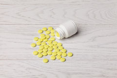 Yellow pills with bottle. On white wooden table Royalty Free Stock Photo
