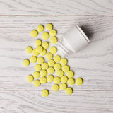 Yellow pills with bottle. On white wooden table Stock Images
