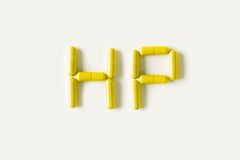 Yellow Pills capsules in shape of word HP. Life concept isolated. Stock Images