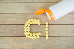 Yellow pills forming shape to Cl alphabet on wood background Royalty Free Stock Photography