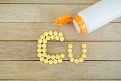 Yellow pills forming shape to Cu alphabet on wood background Royalty Free Stock Photography