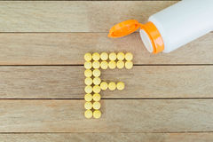 Yellow pills forming shape to F alphabet on wood background Stock Photography