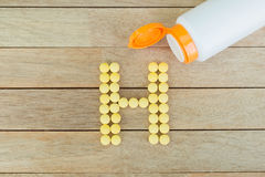 Yellow pills forming shape to H alphabet on wood background Stock Photography