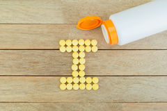 Yellow pills forming shape to I alphabet on wood background Stock Photos