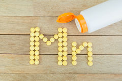 Yellow pills forming shape to Mn alphabet on wood background Royalty Free Stock Photos