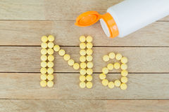Yellow pills forming shape to Na alphabet on wood background Royalty Free Stock Photo