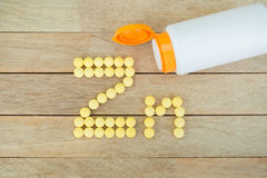 Yellow pills forming shape to Zn alphabet on wood background Royalty Free Stock Photos