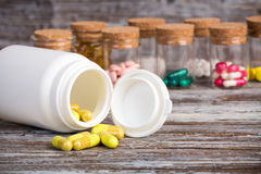 Yellow pills in front of plastic container Royalty Free Stock Photography