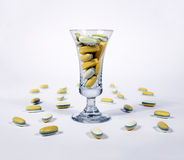 Yellow pills in a glass. Yellow tablests - pills in a glass Royalty Free Stock Images