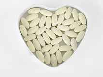 Yellow pills In a heart-shaped box, isolated on the white background. Royalty Free Stock Photography