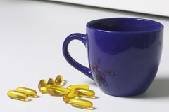 Yellow pills scattered on the white surface of the table. Nearby there is a mug with water and one pill for use. Stock Photography