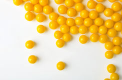 Yellow pills are spilled on the white surface. Stock Image