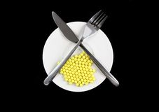 Yellow pills-vitamins ,with fork and spoon Royalty Free Stock Image