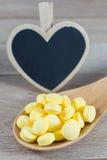 Yellow pills in wooden spoon with blank heart shape blackboard Stock Photography