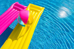 Yellow and pink air beds with beachball on swimming pool water Royalty Free Stock Images
