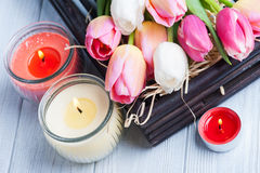 Yellow and pink aroma candles with tulips Stock Photo
