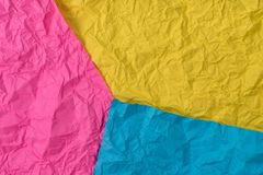Yellow, pink and blue crumpled paper texture as background royalty free stock photos