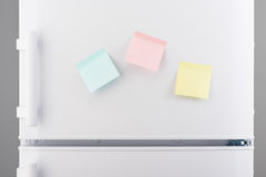 Yellow, pink and blue sticky paper notes on white refrigerator Royalty Free Stock Image