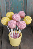 Yellow and pink cake pops on wooden background Royalty Free Stock Image