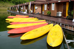 Yellow and pink canoes/kayaks in a row on waterside. Stock Photos