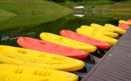 Yellow and pink canoes/kayaks in a row on waterside. Stock Image