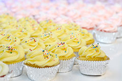 Yellow and Pink Cupcakes. Several yellow and pink cupcakes arranged with sprinkles on top Stock Photo