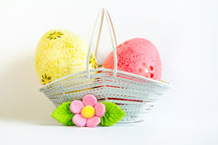 Yellow and pink Easter eggs in a basket with pink flower Stock Photos