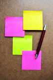 Yellow, pink, green, note paper and red pen on wooden background. Royalty Free Stock Images