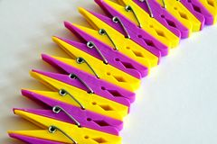 Row from yellow and pink linen clothespins. Yellow and pink linen clothespins on a light background stock image