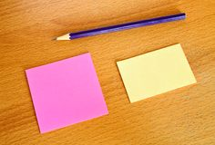 Yellow and pink memo with pencil on table Stock Photography