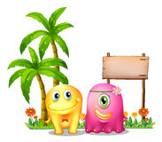 A yellow and a pink monster couple standing in front of the empt Stock Images
