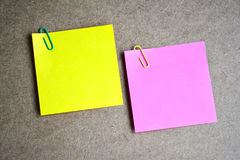 Yellow and pink note paper on wooden background. Stock Images