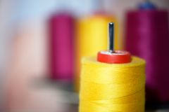 Yellow and pink reels of thread at tailors Stock Photos