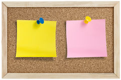 Yellow and pink remainder notes. On cork board, with tacks Stock Photo