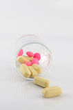 Yellow and pink tablet in dosage glass. Show medice concept Royalty Free Stock Photos