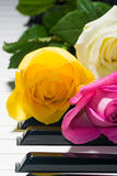 Yellow, pink, tea roses on black and white piano Royalty Free Stock Photography