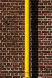 Yellow pipe. In front of a red brick wall, the  is wet paint Stock Images