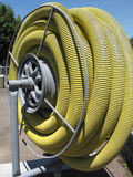 Yellow Pipe on a Reel. Yellow plastic pipe is coiled up on a reel and ready for use stock image