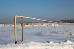 The yellow pipe for supply of liquefied gas is carried out in the Siberian settlement of Blagoe Novosibirsk region through snow in royalty free stock photos