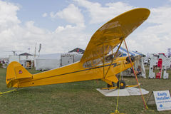 Yellow Piper Cub Plane ready for Alaska. OSHKOSH, WI - JULY 27: Yellow Piper Cub Plane ready for Alaska on display with snowshoe and furs at the 2012 AirVenture Stock Photography