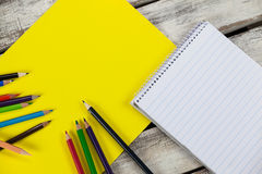 Yellow placard, color pencils and notepad Stock Images