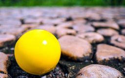 Yellow plastic ball on brown Stones texture and background. Rock royalty free stock photo