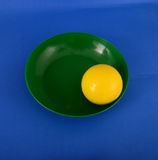 Yellow plastic ball in a gren plate Royalty Free Stock Photos