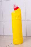 Yellow plastic bottle of cleaning product on tiled floor Stock Photo